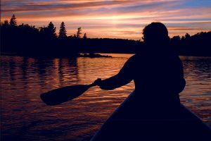 Person Canoeing at sunset in the Boundary Waters