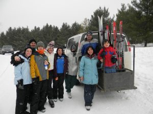People in front of Van with skiis