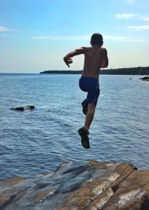 Boy Jumping into Lake Superior in summer